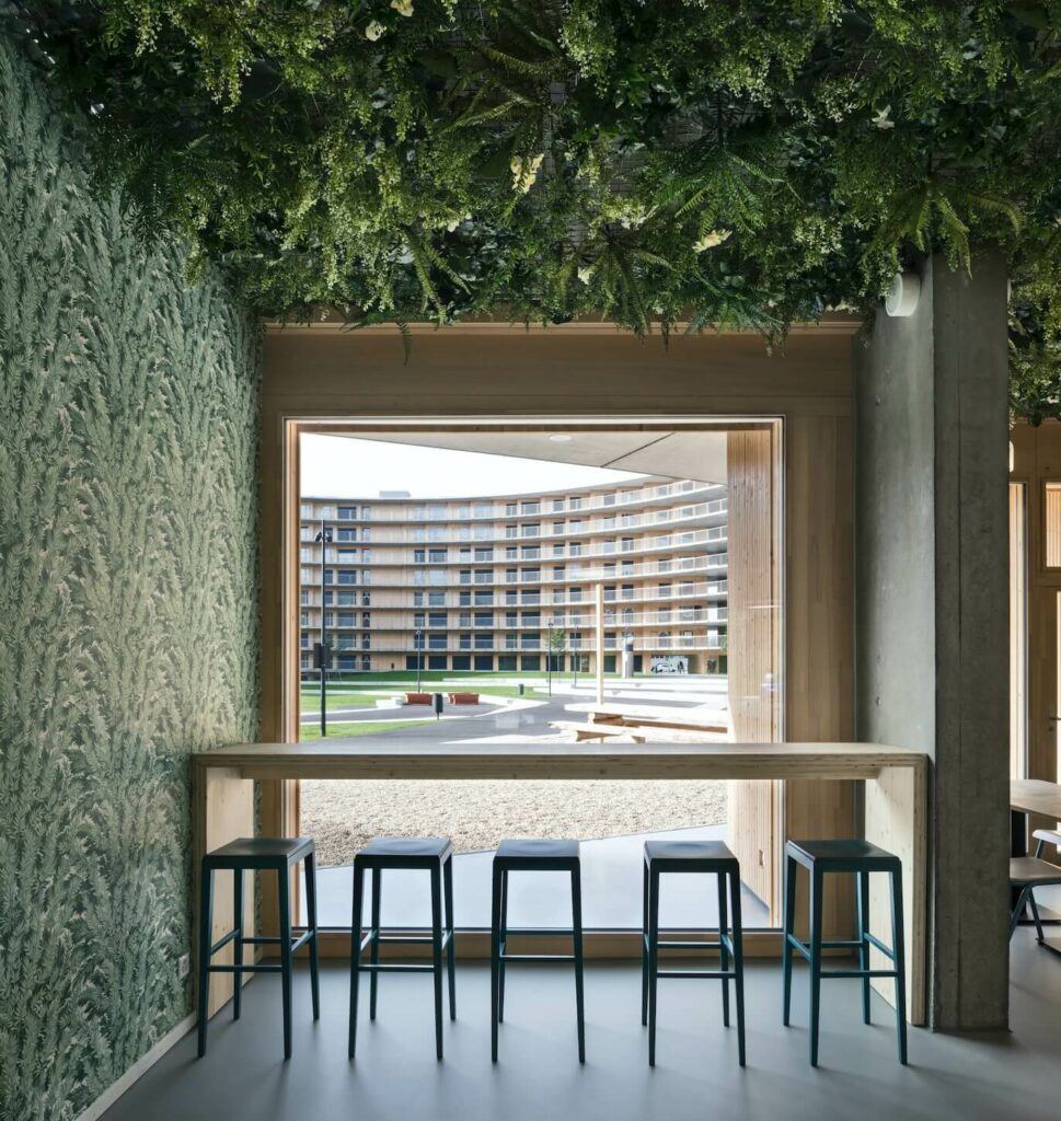 the bar counter which leans on the wallpaper has a ceiling covered in plants