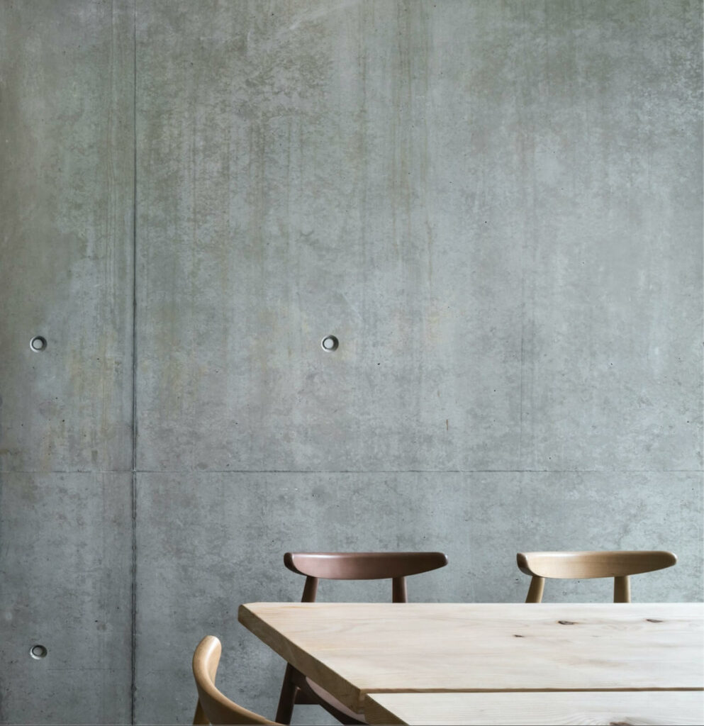 the wooden table and chairs are in front of a concret interior