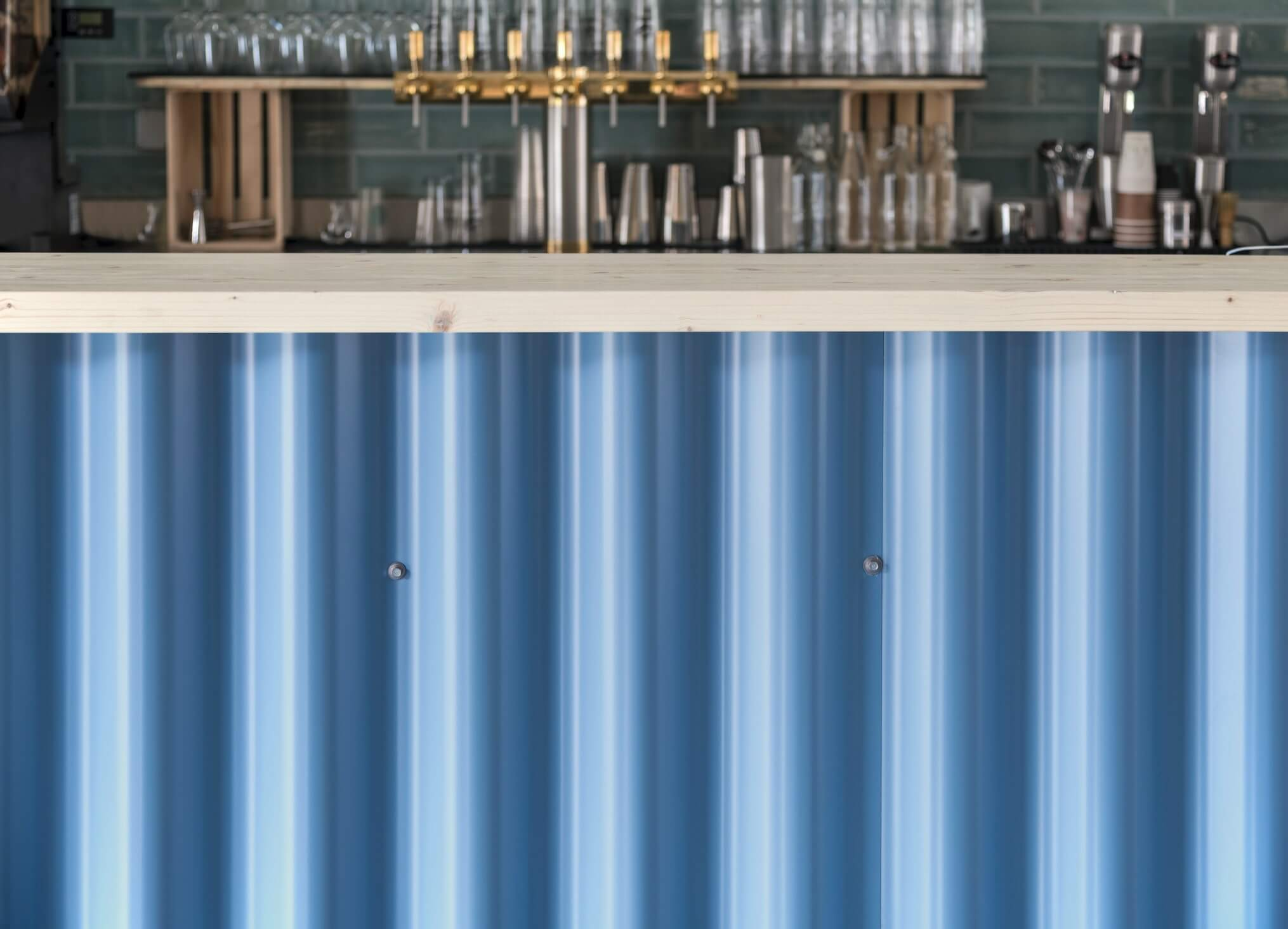 the architecture of the bar has a blue design counter